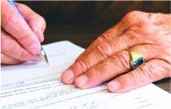man signing document.