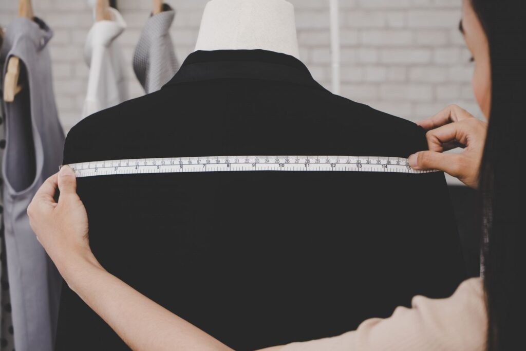 Woman measuring width of mannequins' shoulders.