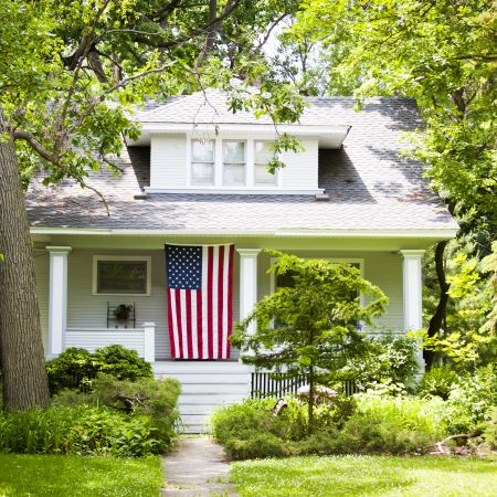 A house that is white with an American flag on the porch.