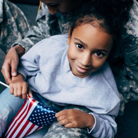 Image of female child holding an American flag sitting on lap of a woman wearing camouflage.
