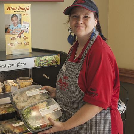 Papa Murphy's employee holding salads.