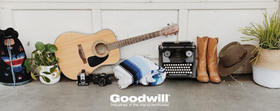 Collection of items including a bag, plants, vintage typewriter, cowboy boots, hat, and guitar.
