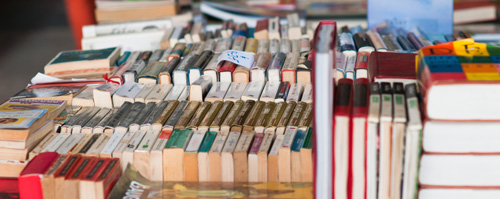Used books arranged on a table, spines facing upward.