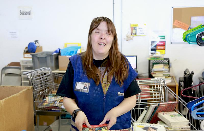 Woman Goodwill employee holding a book.