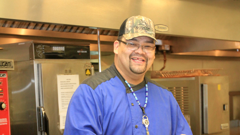 Chef smiling standing in commerical kitchen.