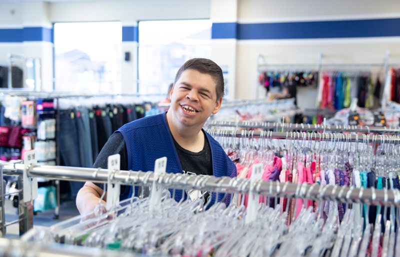 Goodwill employee standing between racks of clothing in Goodwill store.