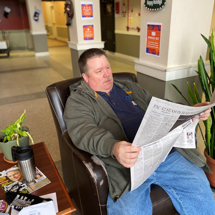 Man reading newspaper, sitting in leather chair.