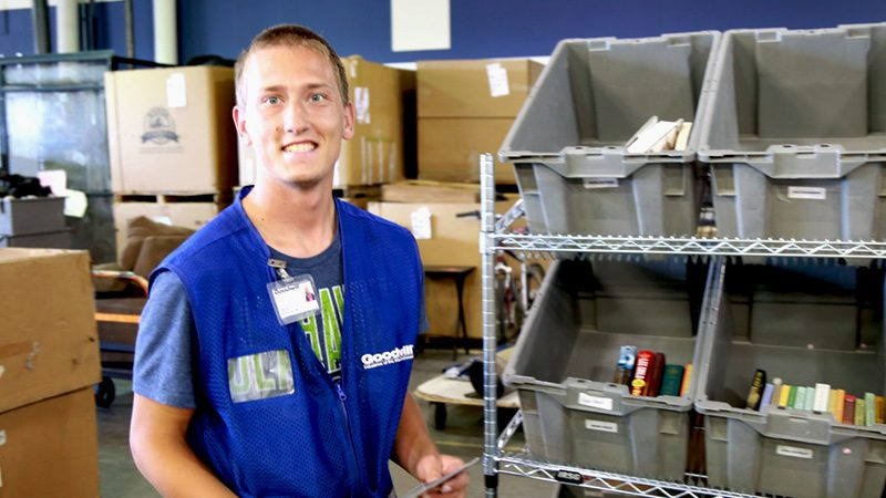Goodwill employee standing in front of bins of books.