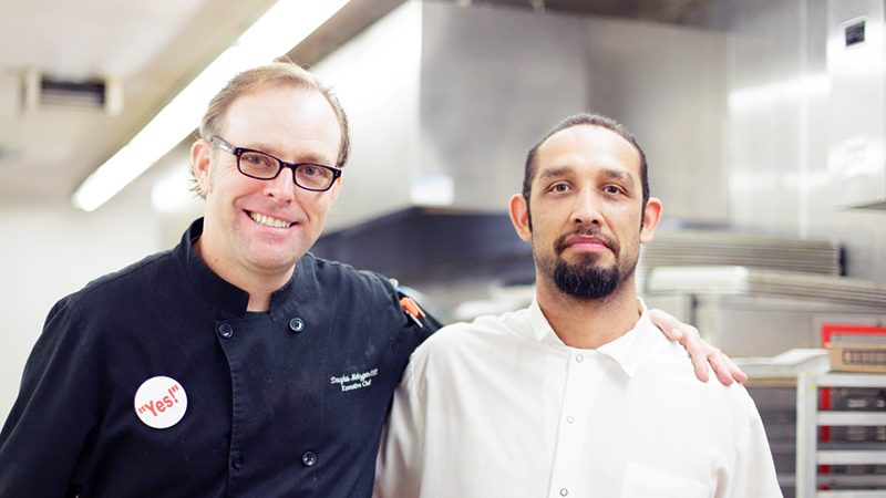 A chef and man posing together in commerical kitchen.