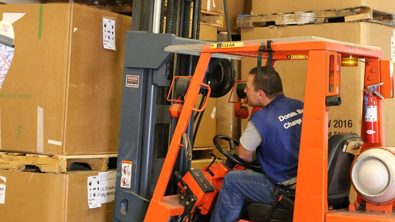 Man using forklift to move large cardboard boxes.