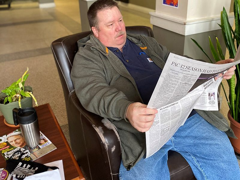 man relaxing and reading newspaper.